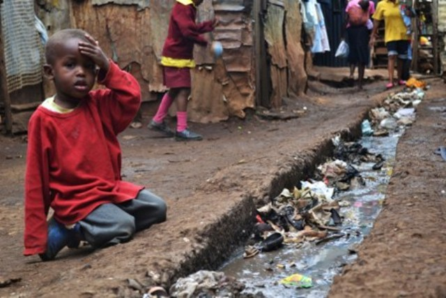 A young boy sits over an open sewer in the Kibera slum, Nairobi. en.wikipedia.org